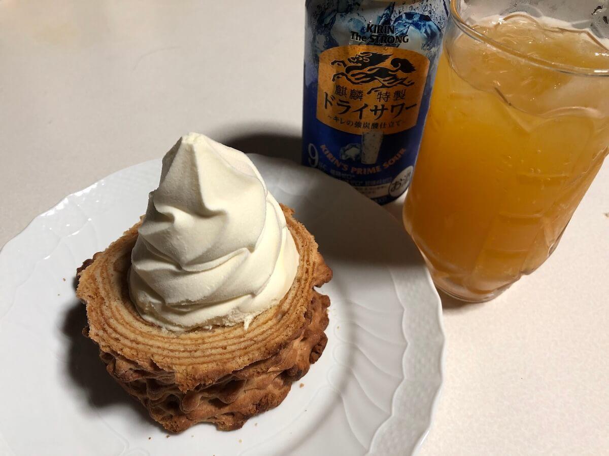 ソフトクリームを乗せたクリスピーロングバウムクーヘンとサジーのお酒写真